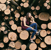 girl among mass of trees from clear cut